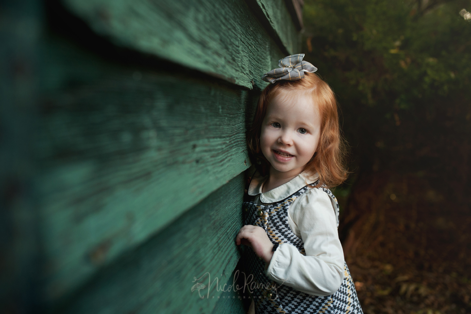 Smiling red headed little girl by green wall